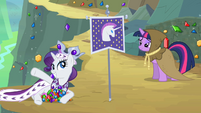 Princess Platinum laying in front of the unicorn flag S2E11
