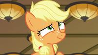 Applejack giving an innocent smile S6E23