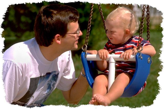 File:Baby in swing with father.jpg