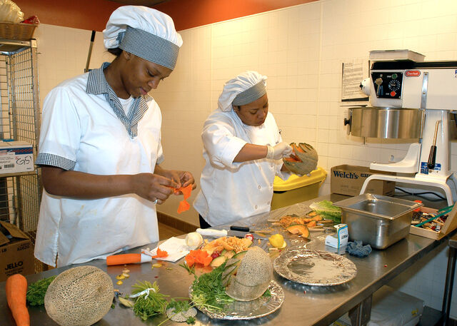 File:US Navy 050308-N-8770A-006 Culinary Specialist Seaman Desiree Thomas of Roanoke Rapids, N.C., left, and Culinary Specialist 3rd Class Mary Wright of Fayetteville, N.C., prepare a food display.jpg