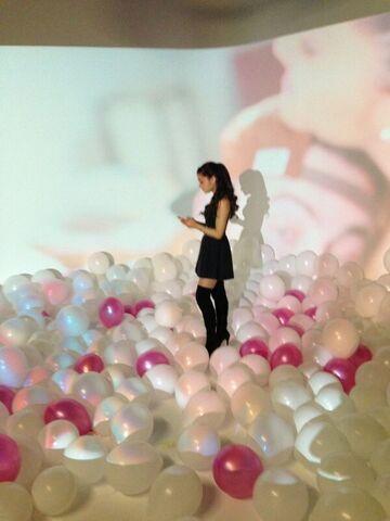 File:Ariana standing on a floor full of balloons.jpg