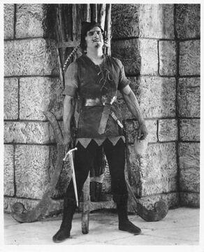 Fairbanks Robin Hood standing by wall w sword