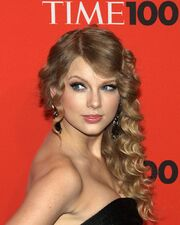 Taylor Swift stands in a Time press area, wearing a black, strapless dress and curled hair