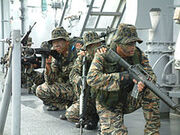 US Navy 040730-N-7720S-045 Members assigned to the Philippine Naval Special Warfare Group (SWAG) Nine One crouch low and move together on the deck aboard the amphibious dock landing ship USS Fort McHenry (LSD 43)
