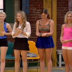 Phoebe looks down at her clipboard as the commencement of auditions is announced.