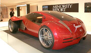 Futuristic two-door concept car displayed in front of a banner labeled 'Minority Report.'