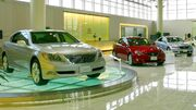 Car showroom displaying three sedans, the nearest on a glass turntable, in front of a reception counter and windows.