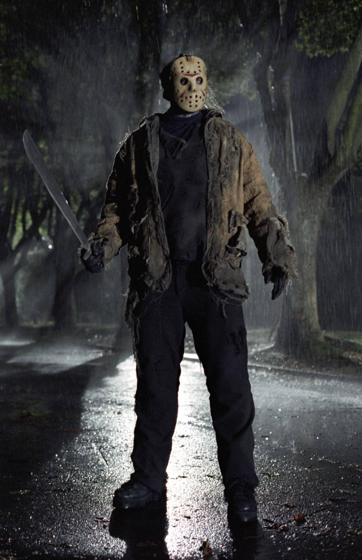 Ken Kirzinger as Jason Voorhees, A man wearing a hockey goalie mask and holding a machete stands in a road at night. The scene is back-lit.