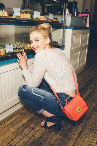 File:Emily Kinney with her fashionable pink sweater looking at treats.jpg