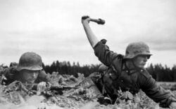 German soldier throws grenade from cover, Operation Barbarossa 1941